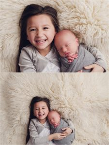 smiling bigger sister with baby brother
