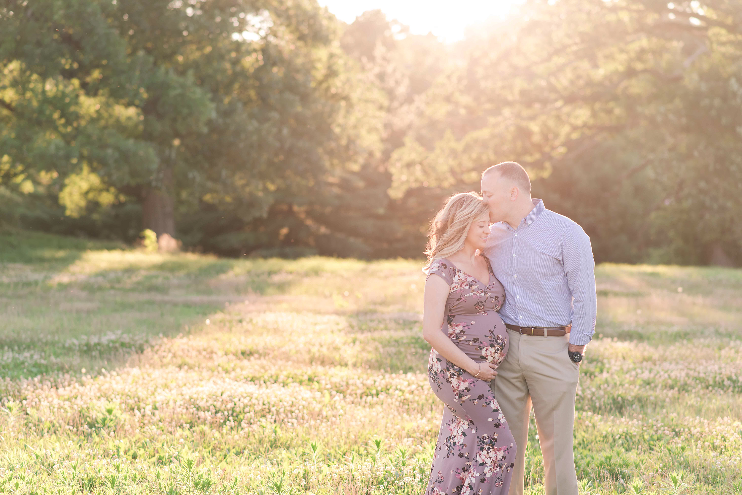 dad kissing pregnant mom in gorgeous light