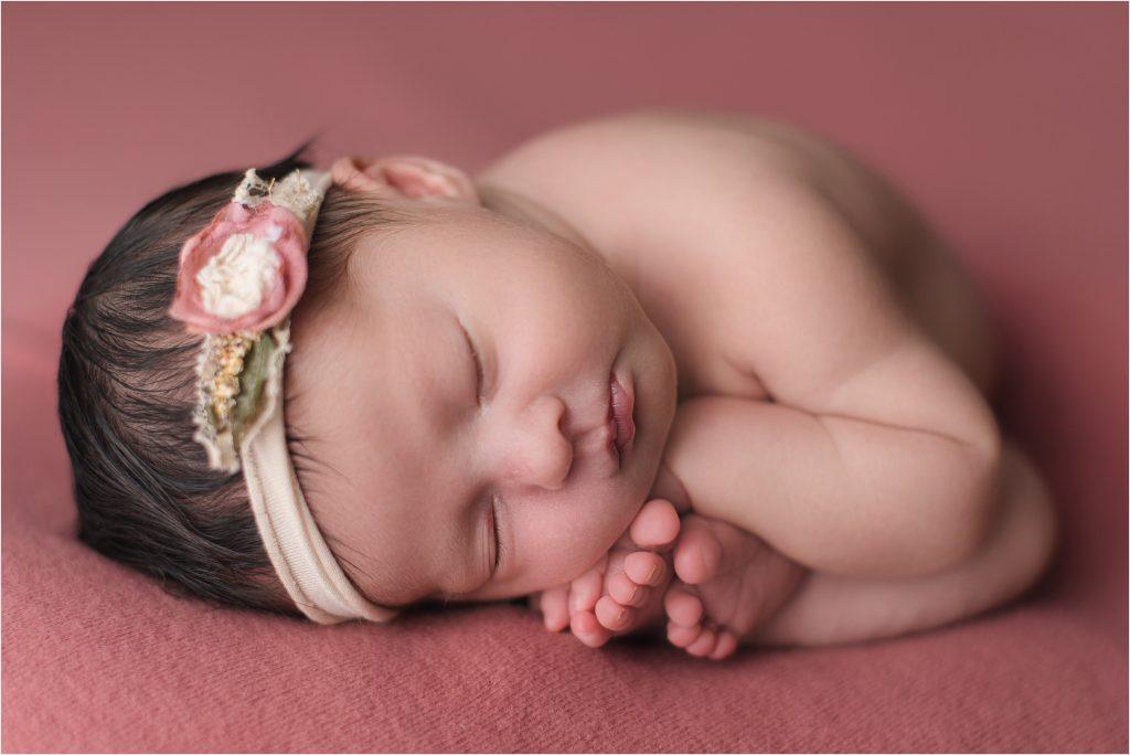 Baby girl on mauve backdrop