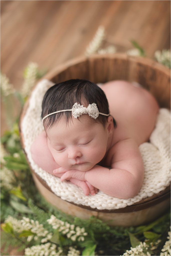 baby girl in rustic bucket with white flowers and green stems