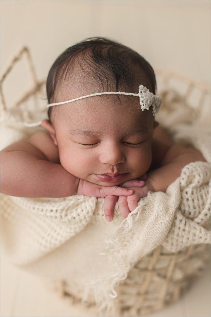 Baby girl on cream backdrop